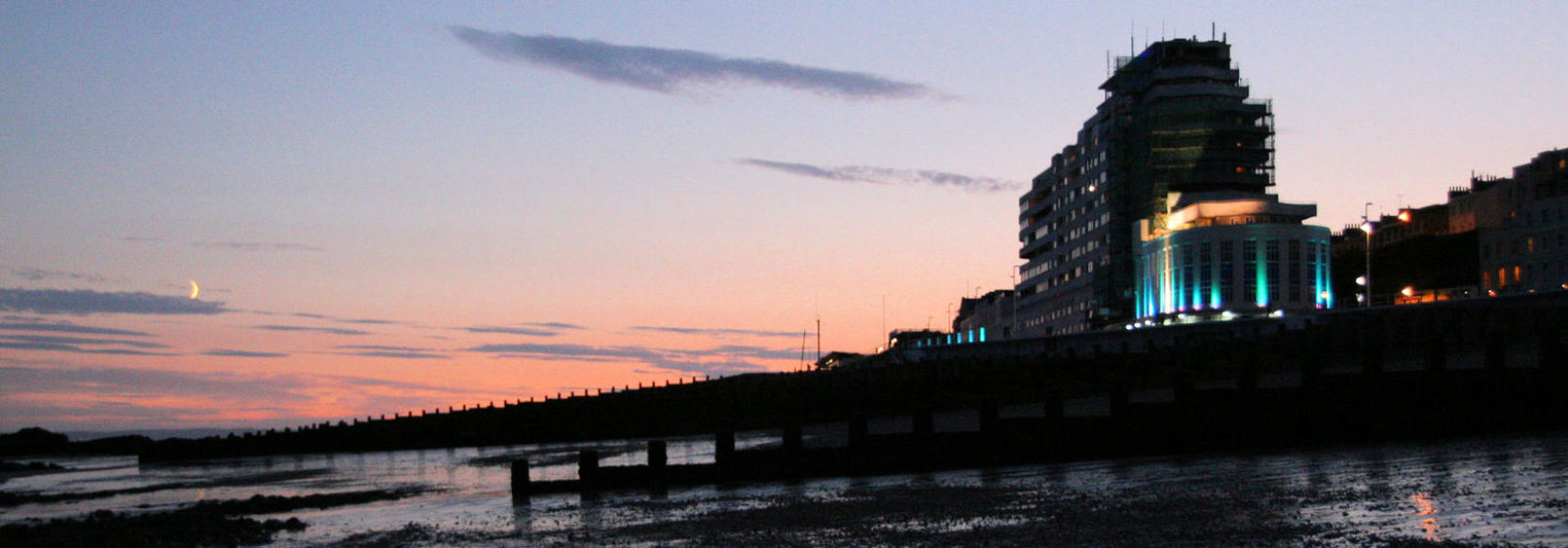 Marine court 'ocean liner' style 1930s flats with blue uplighting at sunset, with beach at low tide