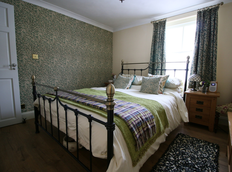 Metal frame bed by window, with willow bough pattern cushions