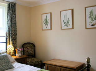bedside cabinet, bedsie chair, oak ottoman and wall with three fern prints