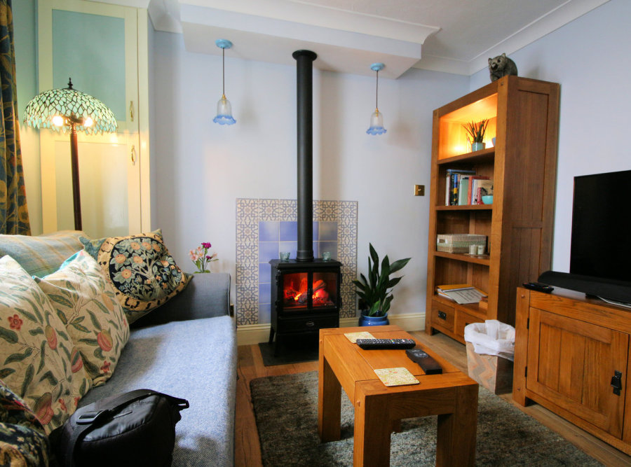 Stove alight, with aspidistra, bookcase, and blue tiled surround