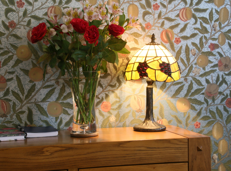 Small Tiffany lamp on console table with vase of red roses