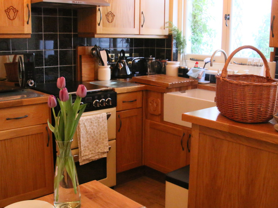oak kitchen units, cooker, butler sink, table with vase of tulips.