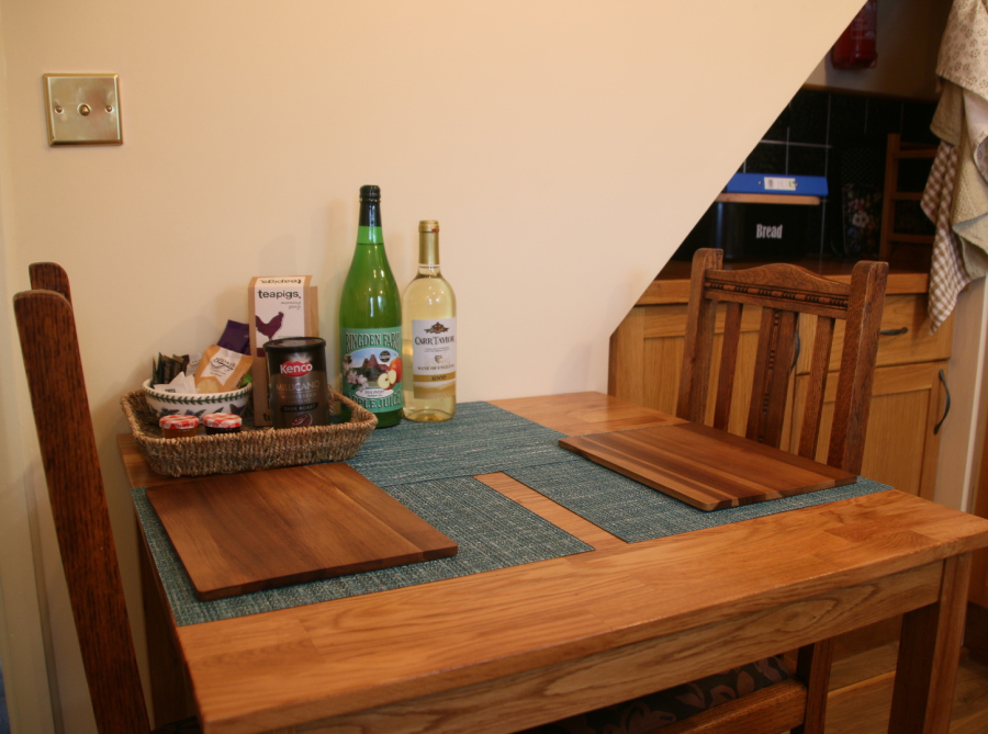 Small oak dining table with two chair, bottles and welcome pack on table