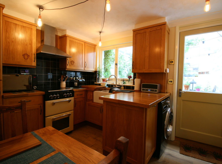 Oak kitchen units, oak work surfaces, retro radio, window to back garden.