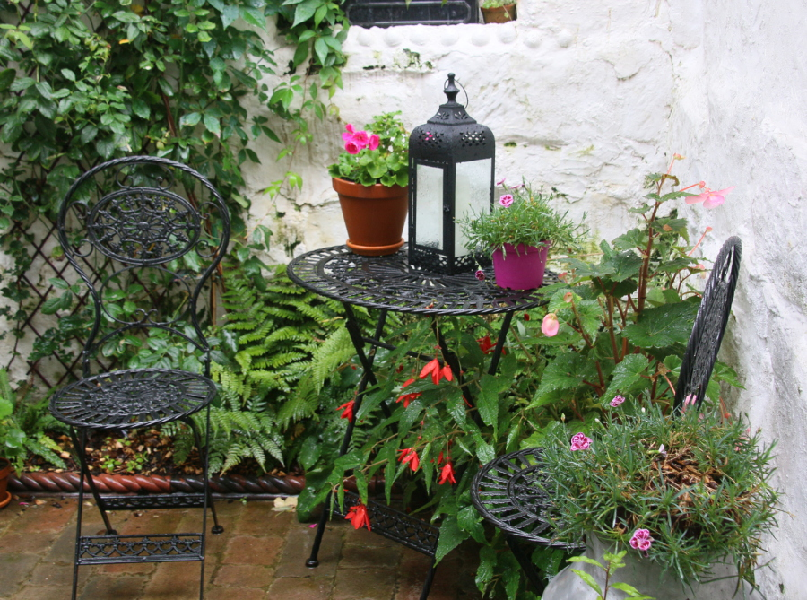 Metal garden chairs and table with lantern, plants in pots