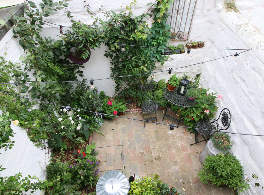 Brick-paved courtyard with pots and edge planting, from above